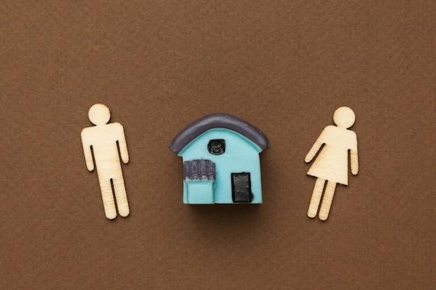 Estatuetas de madeira masculinas e femininas e uma pequena casa em um fundo marrom. postura plana.