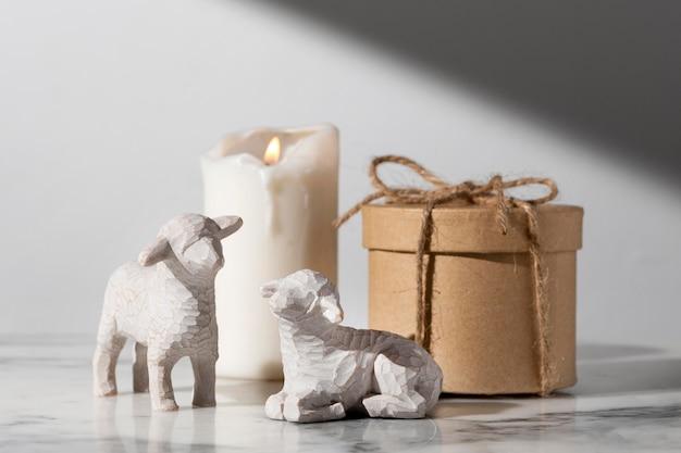 Estatuetas de ovelha do dia da epifania com vela e caixa de presente