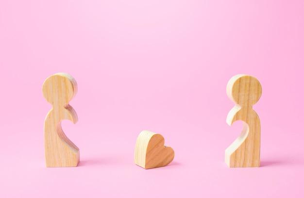Estatuetas de pessoas separadas umas das outras e um coração perdido. separação, fim do amor