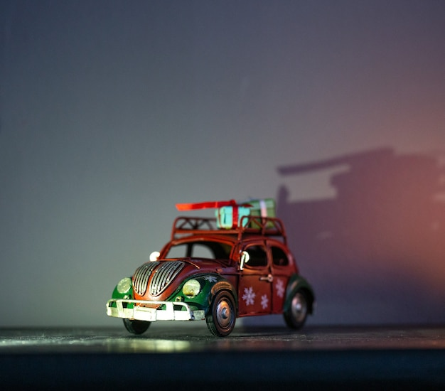 Estatuetas decorativas com tema de natal. uma estatueta de um carro vermelho com presentes no teto.