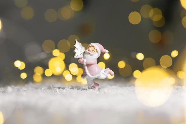 Estatuetas decorativas de um tema de natal. estatueta de papai noel abraçando uma pequena árvore de natal.