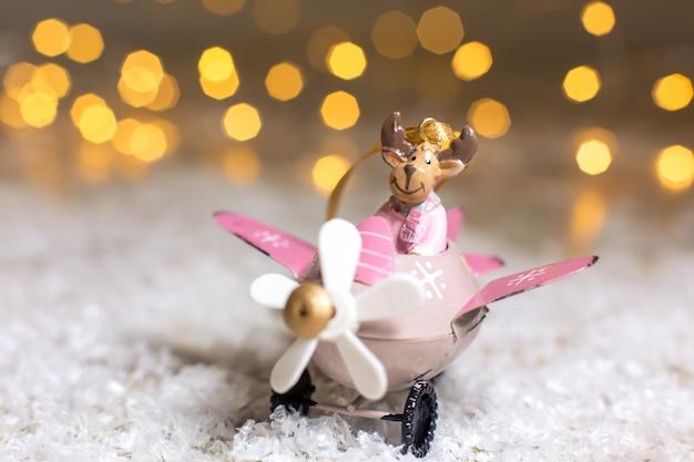 Estatuetas decorativas de um tema de natal. santa s deer em um avião rosa com uma hélice.