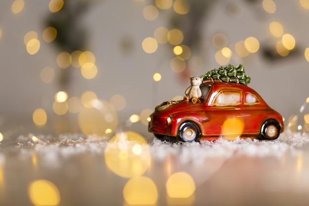 Estatuetas decorativas de um tema de natal. uma estatueta de um carro vermelho no qual um ursinho de pelúcia se senta. decoração da árvore de natal. decoração festiva, luzes quentes de bokeh.
