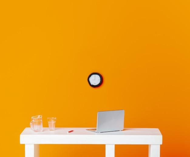 Estatuetas em miniatura laptop e copo d'água em uma mesa com relógio em fundo laranja