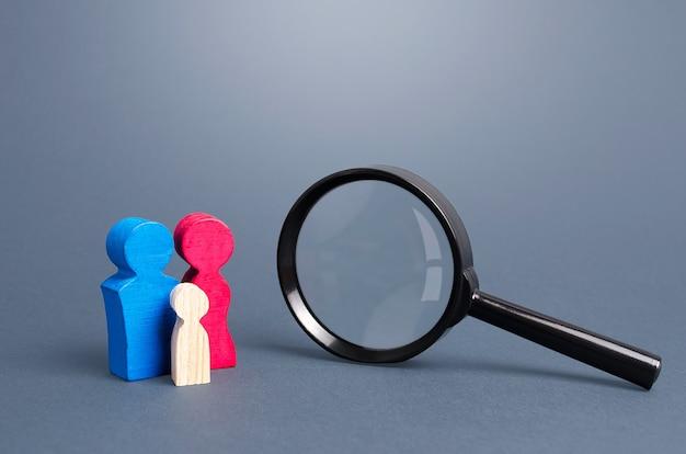 Estatuetas simbolizando a família e lupa. política demográfica. pesquisa de genes