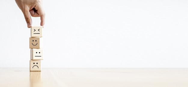 Este bloco quadrado de madeira com emoticons é utilizado para permitir que o cliente avalie sua satisfação após a utilização do serviço. fundo de banner de panorama com espaço de cópia.