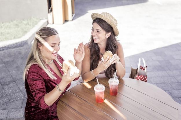 Este é o último. mulher gordinha e alegre olhando para o hambúrguer enquanto quer fazer dieta