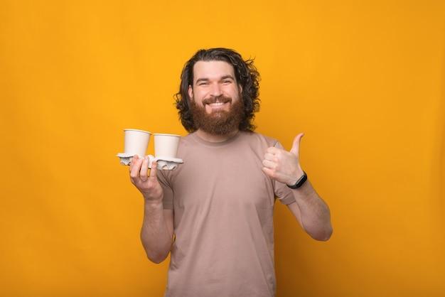 Este é um bom café, jovem barbudo sorridente feliz segurando café para ir e polegar para cima