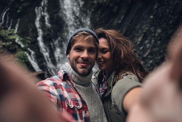 Este entra no quadro! auto-retrato de um lindo casal jovem sorrindo em pé ao ar livre com a cachoeira ao fundo