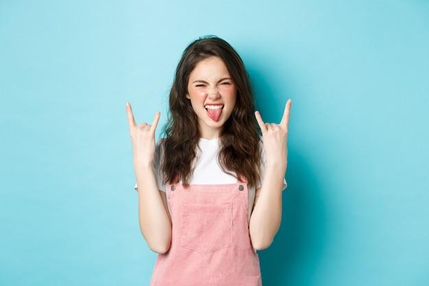 Este evento é demais. jovem atrevida e animada se divertindo, mostrando cartazes de rock-n-roll e dizendo sim, curtindo o show, em pé sobre um fundo azul