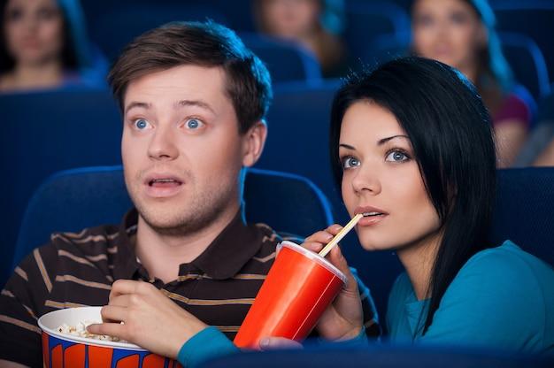 Este filme é tão emocionante! jovem casal animado comendo pipoca e bebendo refrigerante enquanto assiste a um filme no cinema
