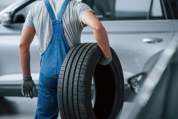 Este vai para o lixo. mecânico segurando um pneu na oficina. substituição de pneus de inverno e verão.