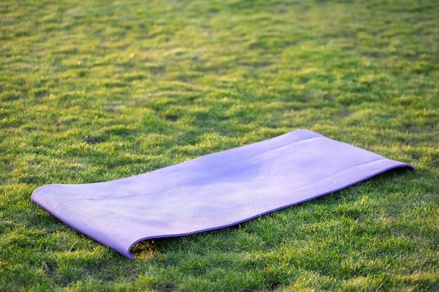 Esteira azul para yoga ou fitness no gramado da grama verde ao ar livre.