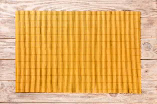 Esteira de bambu amarela sobre fundo de madeira