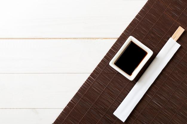 Esteira de bambu e molho de soja com pauzinhos sushi na mesa de madeira branca