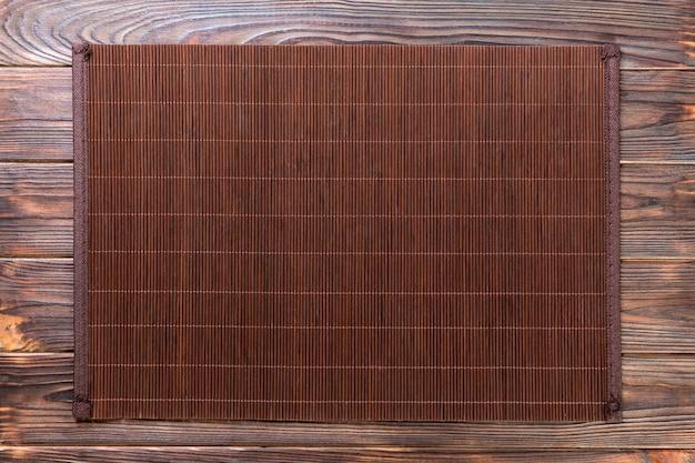 Esteira de bambu escura sobre fundo de madeira