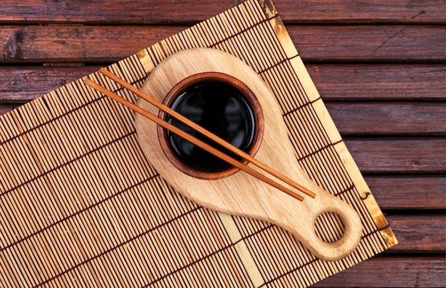 Esteira de bambu, molho de soja, pauzinhos na mesa de madeira escura. vista superior com espaço de cópia