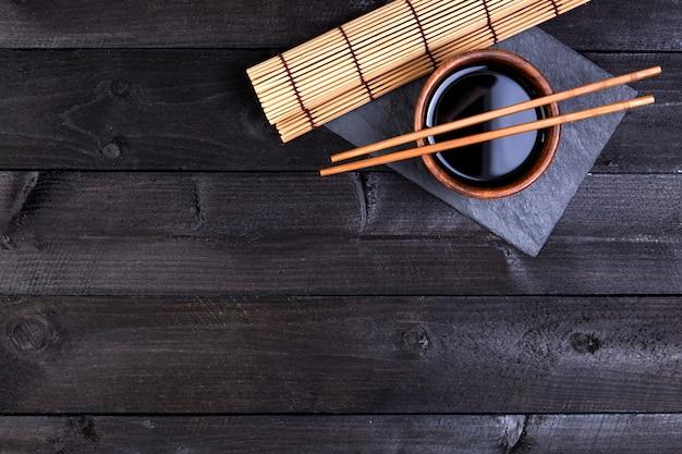 Esteira de bambu, molho de soja, pauzinhos na mesa escura