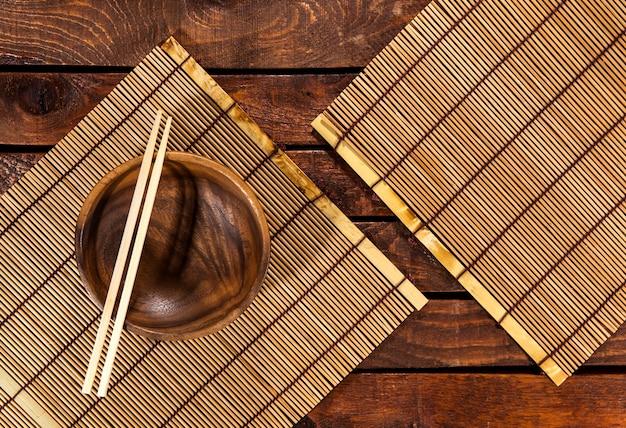 Esteira de bambu na mesa de madeira com tigela e pauzinhos