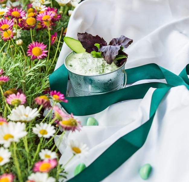 Esteira de piquenique na grama floral e um copo de iogurte.