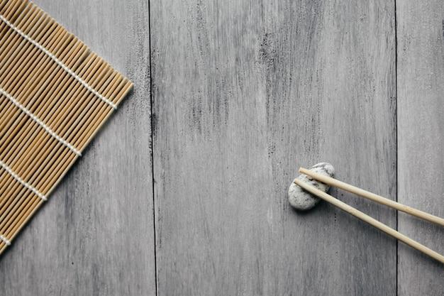 Esteira para rolos e pauzinhos para comida asiática chinesa na luz de fundo de madeira plana