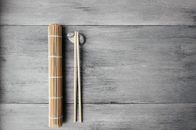 Esteira para rolos e pauzinhos para comida asiática chinesa na luz de fundo de madeira