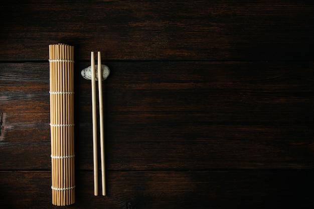 Esteira para rolos e pauzinhos para comida asiática chinesa no fundo escuro de madeira