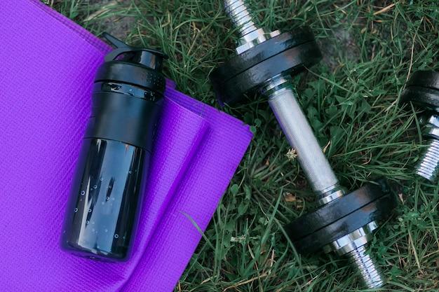 Esteira roxa da ioga, garrafa de água e dumbbell preto na grama verde.