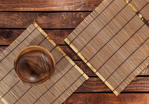 Esteiras de bambu com uma tigela de madeira na mesa de madeira