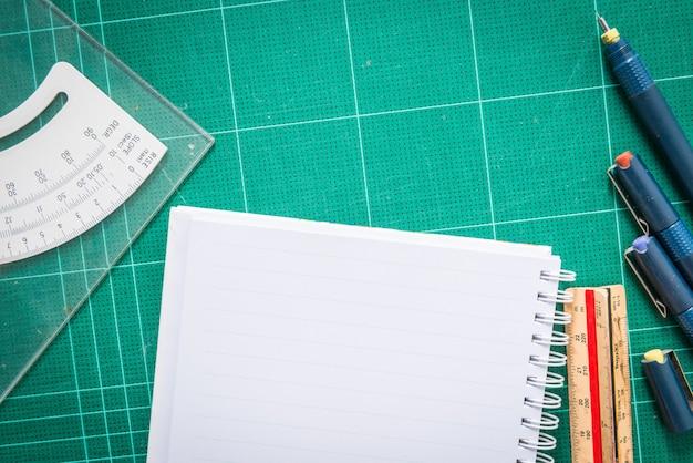 Esteiras de corte, papel, caneta desenhos, ajustar a ferramenta de ângulo, régua de escala no fundo madeira