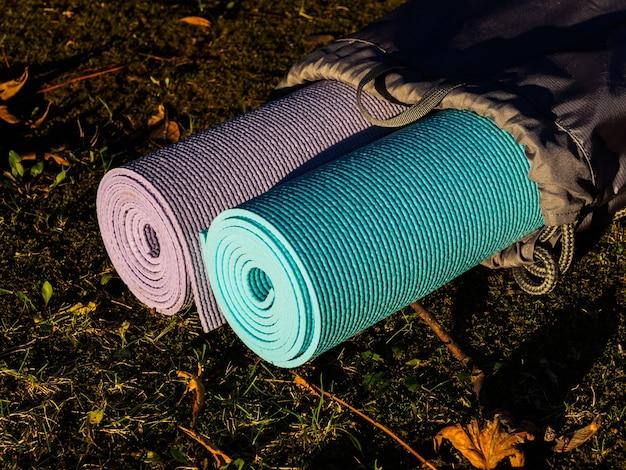Esteiras de ioga em capa cinza na grama.
