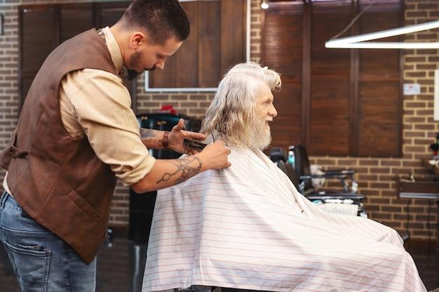 Esteja atento. barbeiro competente em pé perto de seu cliente