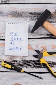 Esteja seguro no trabalho, slogan e ferramentas para consertar ou construir. martelo de vista superior com lonas e chave de fenda em madeira branca.