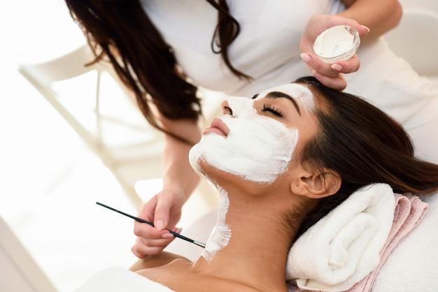 Estética, aplicando uma máscara para o rosto de uma mulher bonita