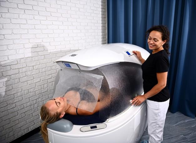 Esteticista ao lado de uma mulher em uma cápsula de spa moderna e recebendo tratamento profissional não invasivo para perda de peso, anticelulite e rejuvenescedor no centro de spa de bem-estar