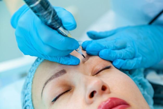 Esteticista aplica maquiagem definitiva nas sobrancelhas tatuagem de sobrancelhas e lábios