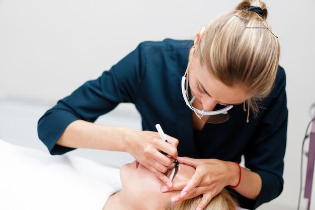 Esteticista aplica marcação nas sobrancelhas.