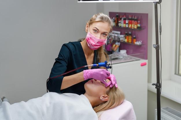 Esteticista aplica tinta permanente nas sobrancelhas.