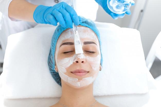 Esteticista aplica uma máscara no rosto de um paciente para cuidar da pele