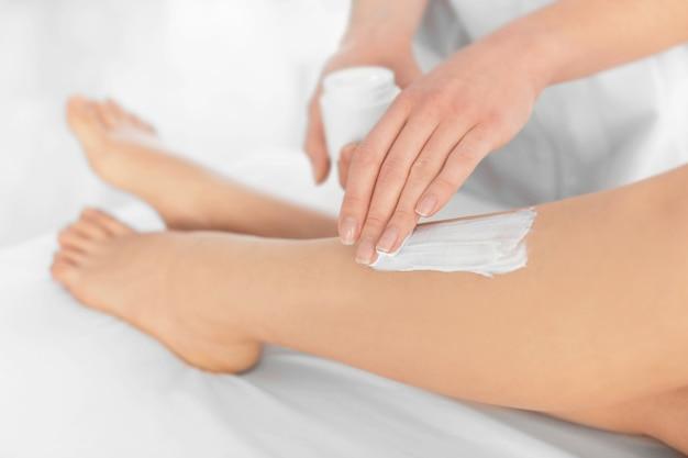 Esteticista aplicando creme hidratante nas pernas femininas em centro de spa