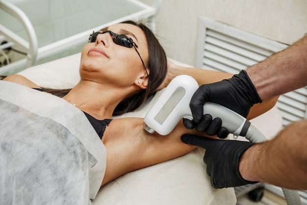 Esteticista aplicando depilação ou depilação a laser na zona das axilas