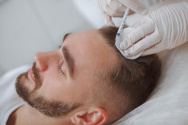 Esteticista aplicando injeções de tratamento contra queda de cabelo no couro cabeludo de um cliente do sexo masculino