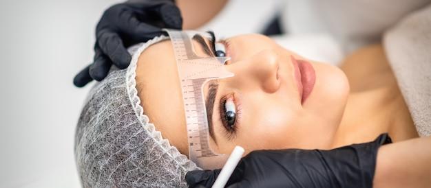 Esteticista aplicando maquiagem definitiva nas sobrancelhas por máquina de tatuagem