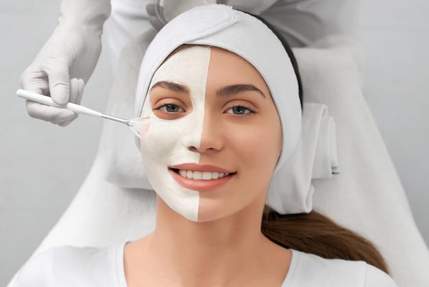 Esteticista aplicando máscara branca especial no rosto para mulher