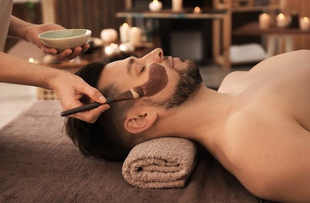 Esteticista aplicando máscara cosmética no rosto do homem em salão de spa