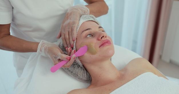 Esteticista aplicando máscara facial de argila no rosto da mulher. procedimento estético. vista lateral.