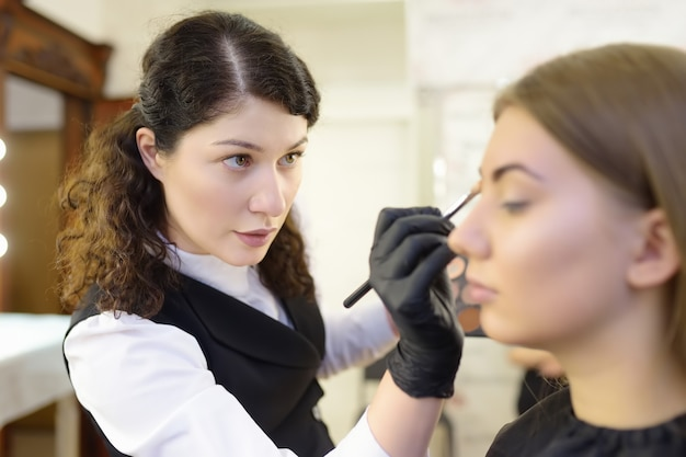 Esteticista, aplicando o tom da fundação usando pincel especial no rosto jovem modelo bonito. cuidados faciais e maquiagem