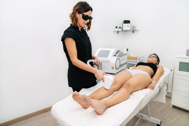 Esteticista aplicando tratamento de depilação a laser em uma mulher na coxa