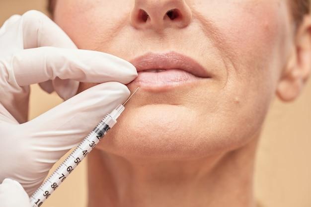 Esteticista com luvas de proteção fazendo injeção para mulher madura