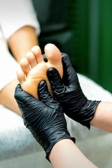 Esteticista com luvas protetoras de borracha fazendo massagem na sola do pé feminino em um spa de salão de beleza
